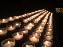 Votive candles in a church. Votive candles or prayer candles in a church intended to be burnt as a votive offering in an act of Christian prayer stock images