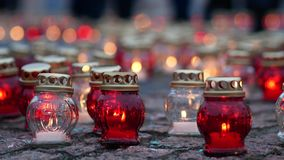 Votive candles on a tile. Grave candles burn on the ground. Mourning concept. Close up stock footage