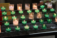 Votive kaarsen werden aangestoken in een kerk (Frankrijk) Stock Foto