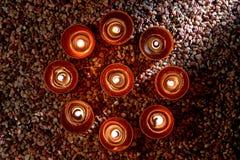 Votive Kerzen, die im geistigen Kreis brennen Stockfotografie