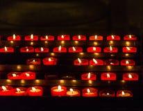 Votive stearinljus i kyrka Arkivbilder