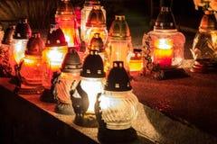 Votive stearinljus lyktabränning på gravarna i slovakisk kyrkogård på nattetid All Saints& x27; Dag Helgon för högtidlighet allra arkivbilder