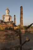 Votive stearinljus och jätte- Buddha på Wat Mahathat i Sukhothai, Th Arkivfoton