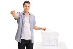 Voto de carcaça do eleitor na urna de voto e apontar na câmera Foto de Stock