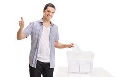 Voto de carcaça do eleitor na urna de voto e da fatura no polegar acima fotografia de stock royalty free