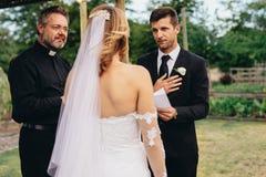 Votos da leitura do noivo em seu casamento imagens de stock royalty free