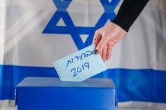 Votos israelíes de la mujer en un colegio electoral el día de elección Ciérrese para arriba de la mano fotografía de archivo
