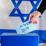 Votos israelitas da mulher em uma estação de vatação no dia de eleição Feche acima da mão fotografia de stock
