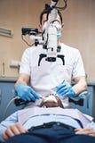 Votre voie ? un nouveau sourire lumineux Regard masculin de dentiste au patient ? l'aide du microscope binoculaire dentaire profe image libre de droits