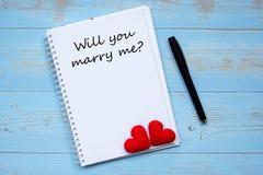 VOUS M'ÉPOUSEREZ ? mot sur le carnet et le stylo avec la décoration rouge de forme de coeur de couples sur le fond en bois bleu d photos stock