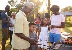 Vovô e neto que grelham em um assado da família imagens de stock