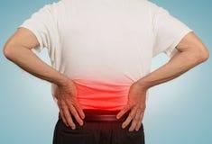 Vovô do ancião que mantém sua mais baixa parte traseira dolorosa colorida no vermelho Fotografia de Stock