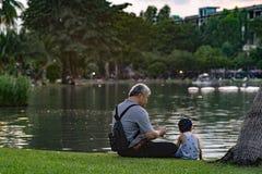 Vovô e sobrinho que relaxam no parque do chatuchak Fotos de Stock