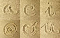 Vowels and arroba handwritten in the sand. Golden colors Stock Photo