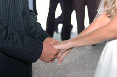 Vows. Couple holding hands reciting vows at wedding Stock Image