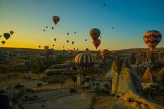 Voyage à Goreme, Cappadocia, Turquie Le lever de soleil dans les montagnes avec beaucoup de ballons chauds d'air dans le ciel photographie stock libre de droits