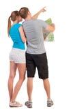 Voyage arrière de vue des jeunes couples regardant la carte. Photographie stock libre de droits