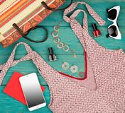 Voyage concept - set of woman stuff with dress, smart phone, bag, notepad, accessory and nail polishes. On blue wooden desk Royalty Free Stock Photography