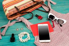 Voyage concept - set of woman stuff with dress, smart phone, bag, notepad, accessory and nail polishes on wooden desk. Voyage concept - set of woman stuff with royalty free stock image