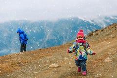 Voyage d'hiver de famille - petite fille et garçon trimardant en montagnes Photographie stock