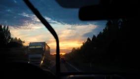 Voyage de famille La famille va en voiture sur la route Route de nuit, coucher du soleil banque de vidéos