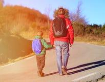 Voyage de famille - le père et le fils avec des sacs à dos marchent sur la route Photographie stock libre de droits
