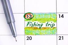 Voyage de pêche de rappel dans le calendrier avec le stylo Photo stock