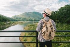 Voyage de randonneur de jeune homme se tenant sur le pont de corde de suspension photo stock