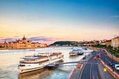 Voyage et concept europ?en de tourisme Le Parlement et rive à Budapest Hongrie avec les bateaux guidés pendant le coucher du sole image libre de droits