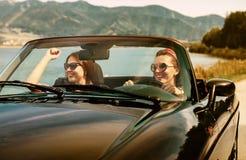 Voyage femelle de deux amis dans la voiture de cabriolet Image stock