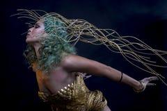 Voyage, femme latine avec les cheveux verts et costume d'or avec le handma Photo stock