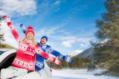 Voyage heureux de couples en la voiture en hiver Image stock