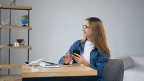 Voyage heureux de vacances de planification de jeune femme utilisant le téléphone intelligent à la maison banque de vidéos