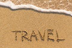 VOYAGE - mot dessiné sur la plage de sable Images stock