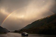 Voyage nuageux d'arc-en-ciel de montagnes de vitesse de voiture de route de route Image stock