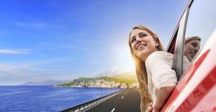Voyage ou vacances Belle fille blonde dans la voiture sur la route vers la mer Images libres de droits