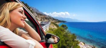 Voyage ou vacances Belle fille blonde dans la voiture sur la route vers la mer Image libre de droits