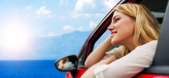 Voyage ou vacances Belle fille blonde dans la voiture sur la route vers la mer Image stock