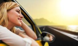 Voyage ou vacances Belle fille blonde dans la voiture sur la route vers la mer au coucher du soleil Photographie stock libre de droits
