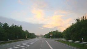 Voyage par la route pendant le lever de soleil banque de vidéos