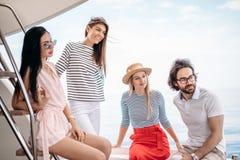 Voyage, seatrip, amitié et concept de personnes - amis s'asseyant sur la plate-forme de yacht Photo stock