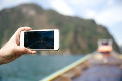 Voyage sur le bateau de longue queue avec un téléphone à disposition image stock