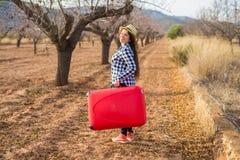 Voyage, tourisme et concept de personnes - jeune femme heureuse allant voyager par avec la valise rouge et souriant au-dessus de  photo stock