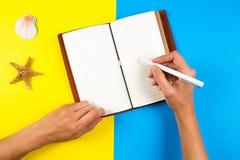 Voyage, vacances, concept d'été Écriture de main de femme dans le carnet au-dessus du fond bleu et jaune Images libres de droits