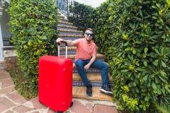 Voyage, vacances et concept de personnes - touriste beau heureux d'homme s'asseyant sur des escaliers avec la valise et le sourir photos stock