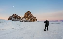 Voyageant en hiver, trépied d'appareil-photo de transport de photographe chez le lac Baïkal congelé en Sibérie, Russie Images libres de droits