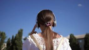 Voyages de jeune fille dans la ville touriste de femme marchant le long de la rue la fille dans des écouteurs avec le sac à dos s banque de vidéos