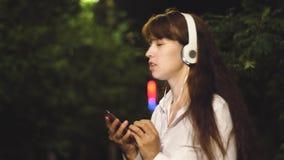 Voyages gais de fille dans la ville de nuit la jeune fille dans les écouteurs et le smartphone écoute la musique, danse et clips vidéos
