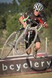 Voyages juniors de coureur de Cyclocross au-dessus de barrière Photographie stock