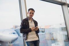 Voyageur à l'intérieur de terminal d'aéroport Jeune homme à l'aide du téléphone portable et attendant son vol Photo stock